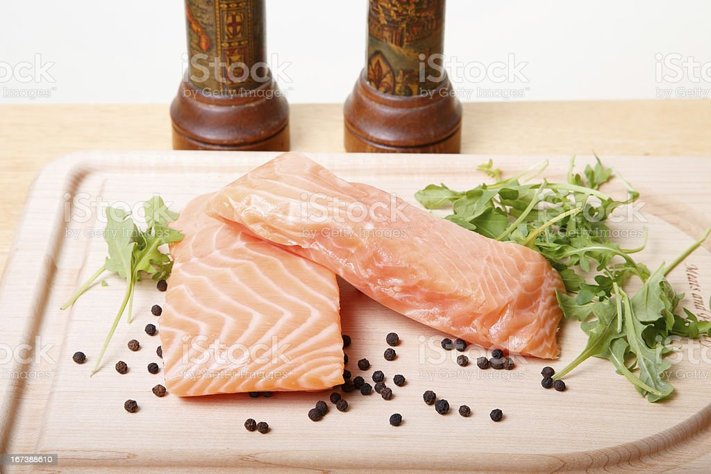 Salmon Fillets on Board with Peppercorns and Arugula royalty-free stock photo