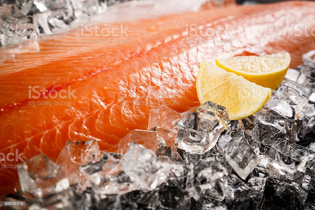 Salmon fish on ice on a black table stock photo