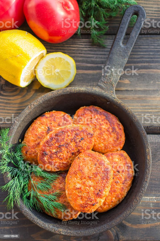 salmon fishcakes in a cast iron skillet, tomatoes and lemon stock photo