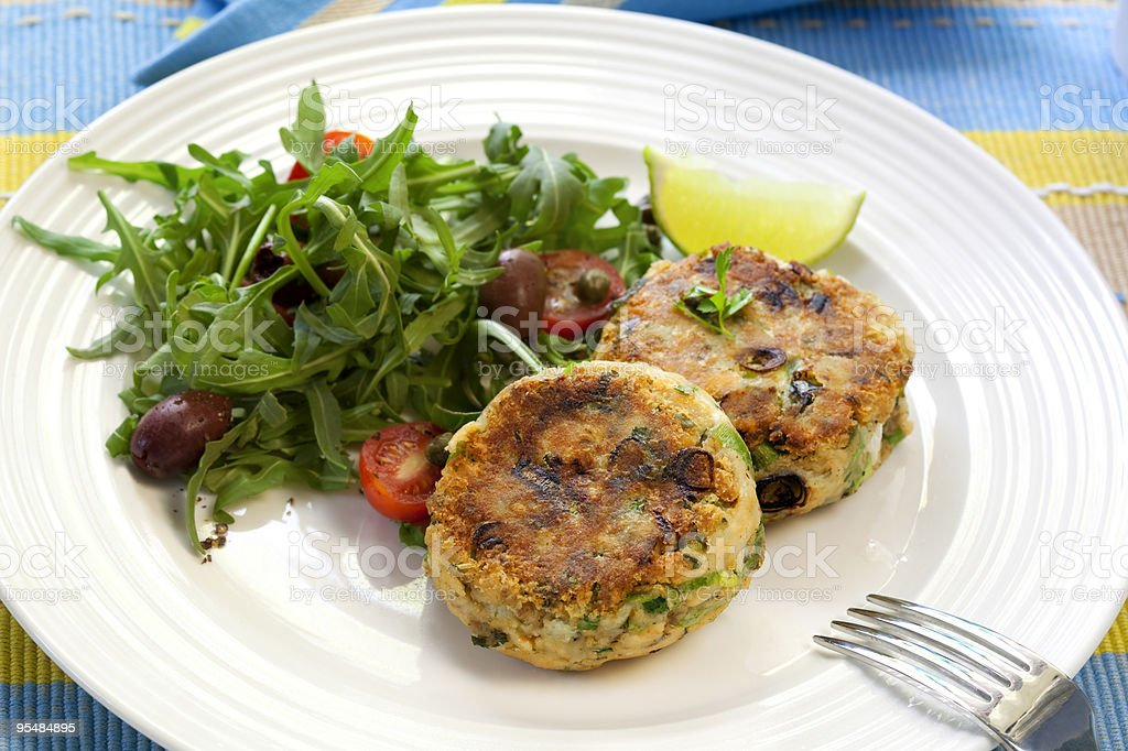 Salmon fishcakes served with salad on a white plate stock photo