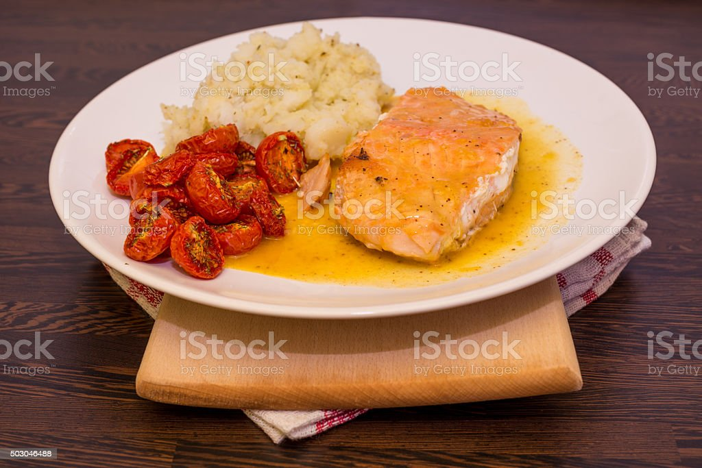 Salmon In Orange Sauce Served With Dry Tomatoes And Potatoes stock photo