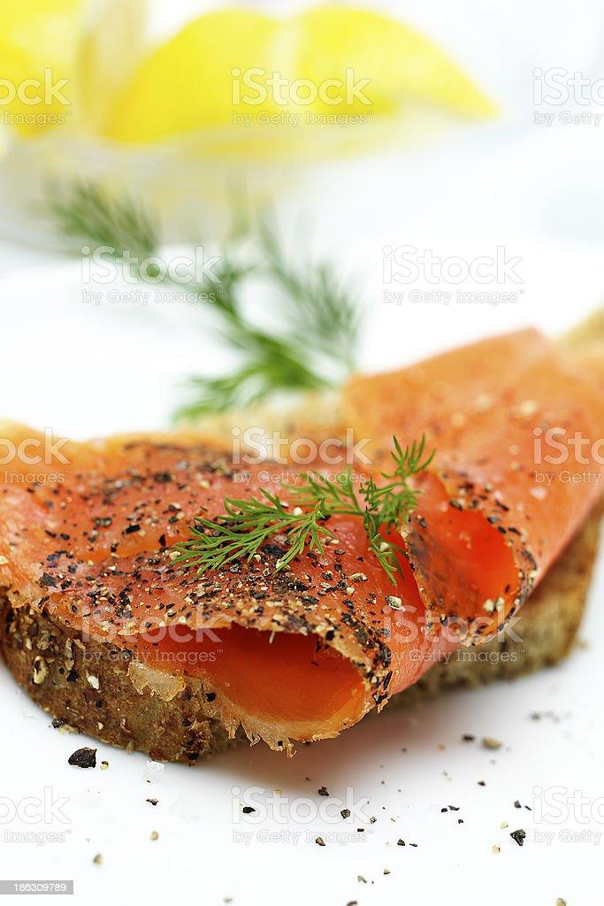 Salmon on brown bread with lemon stock photo
