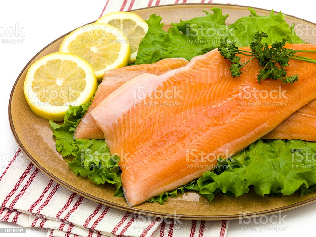 Salmon on Plate with Lettuce and Lemons stock photo