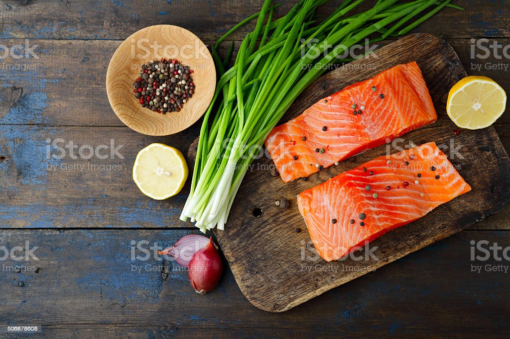 Salmon, onion and spice on cutting board stock photo