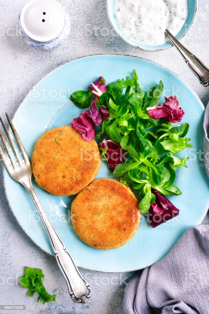 Salmon patties with mix salad leaves and yogurt sauce stock photo