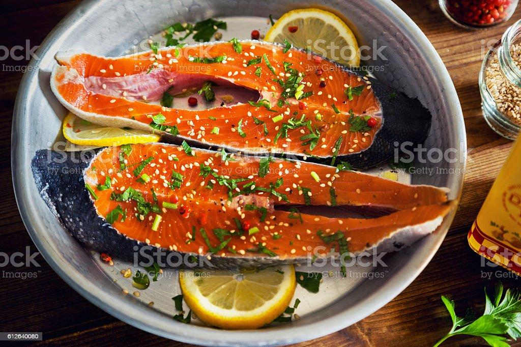 Salmon slices seasoned with lemon, sesame oil and parsley stock photo