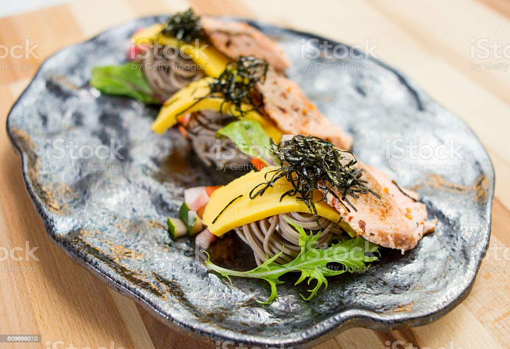 Salmon Soba with noodle, herbs and seaweed on black platter stock photo
