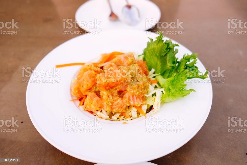 salmon spicy salad thai style on the white dish stock photo