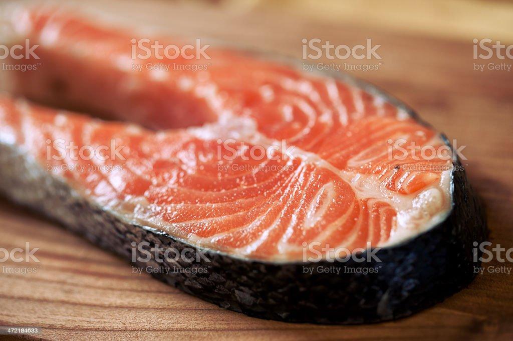Salmon steak isolated on wood stock photo