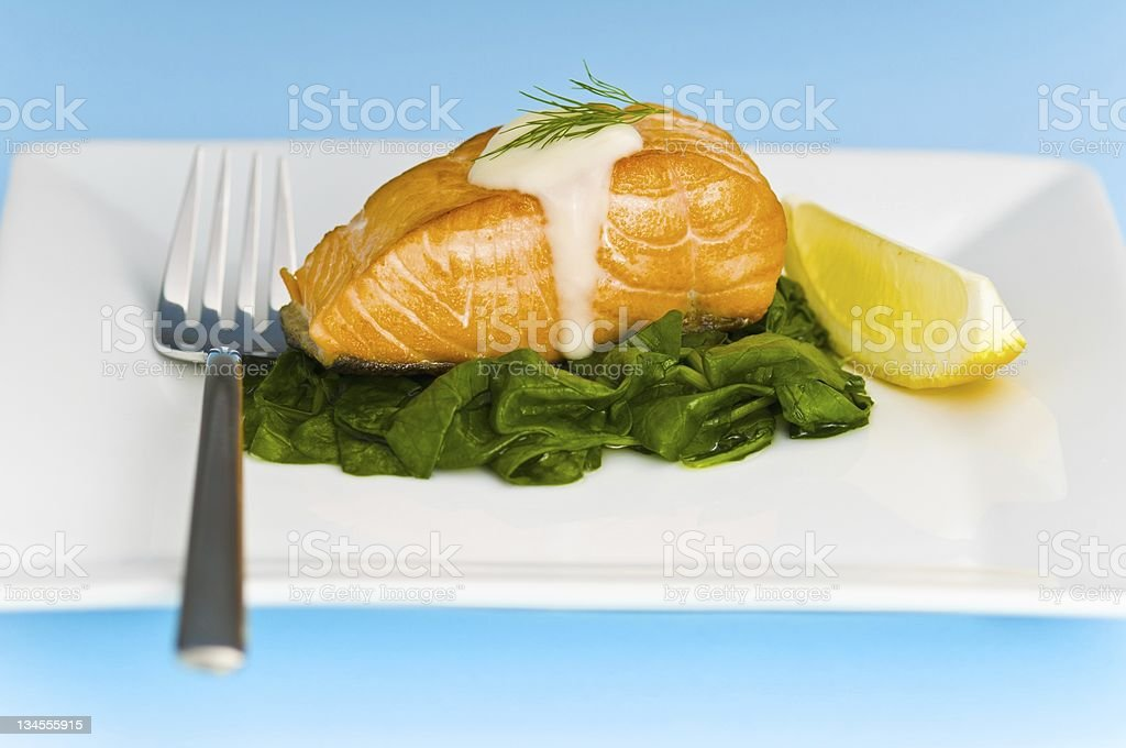 Salmon steak on spinach, decorated with lemon, sauce and fork royalty-free stock photo