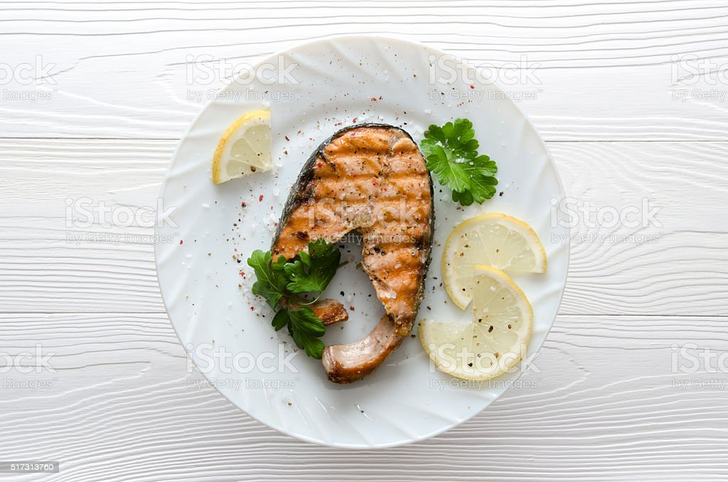 salmon steak on  white plate on  white wooden background stock photo