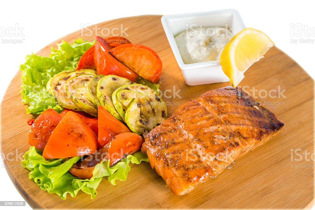 Salmon steak with grilled vegetables, sauce and lemon stock photo