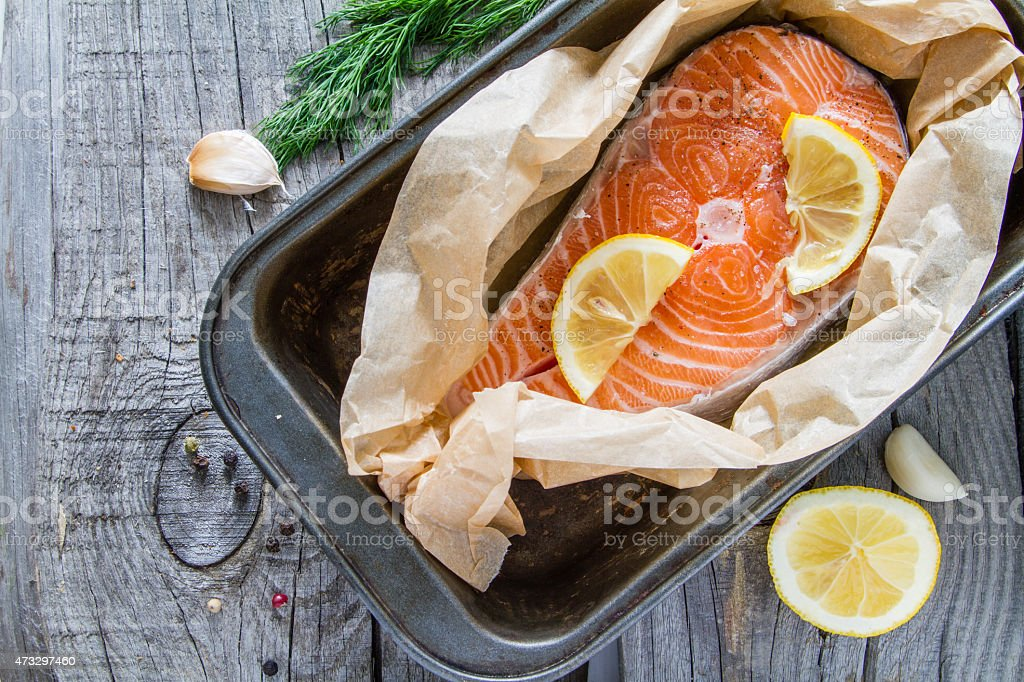 Salmon steak with pepper, dill, lemon, garlic on baking paper stock photo