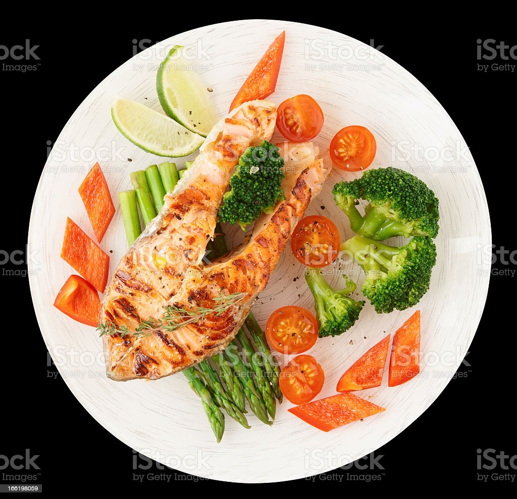 Salmon steak with vegetables isolated on black royalty-free stock photo