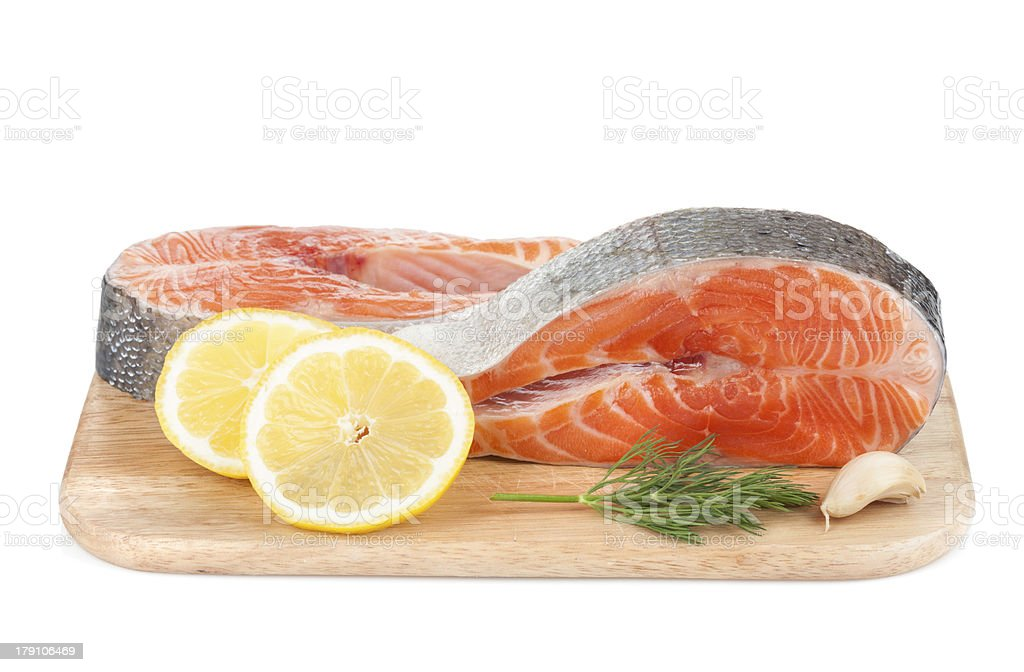 Salmon steaks on cutting board with lemons and herbs royalty-free stock photo