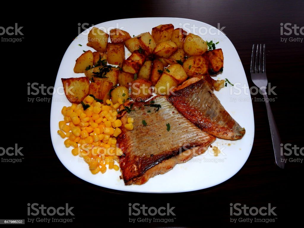 salmon with baked potatoes and corn stock photo