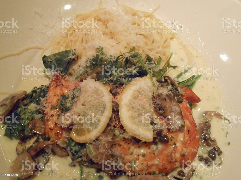 Salmon with Mushrooms and Thin Pasta on Plate in Restaurant. stock photo