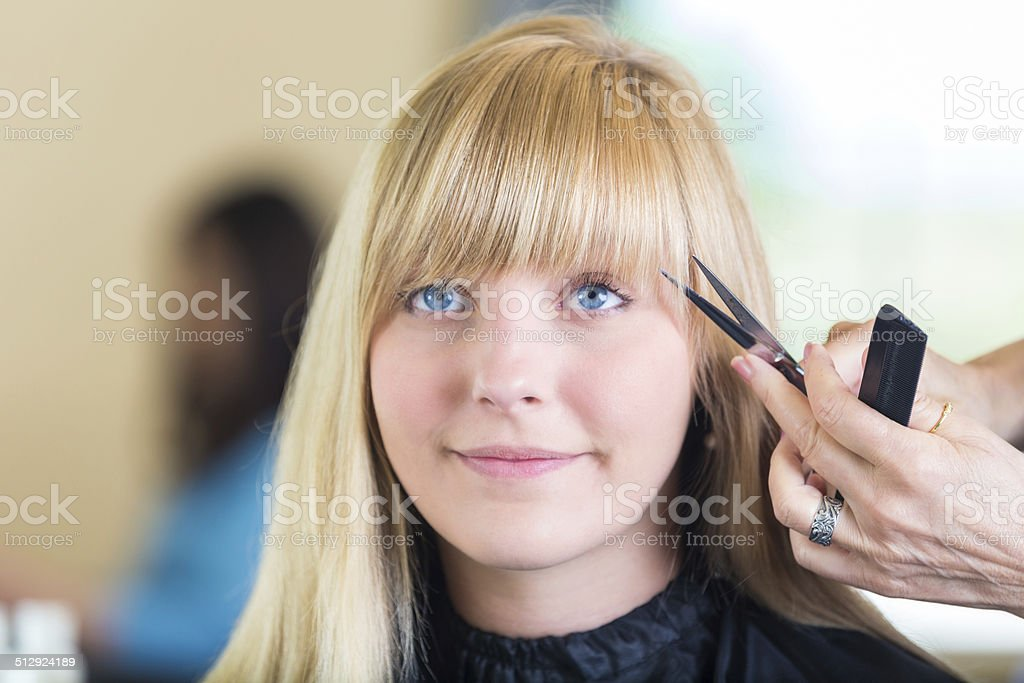 Salon client having bangs trimmed by professional hairstylist stock photo