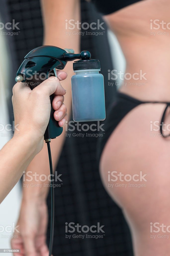 Salon employee using airbrush to give client artificial spray tan stock photo