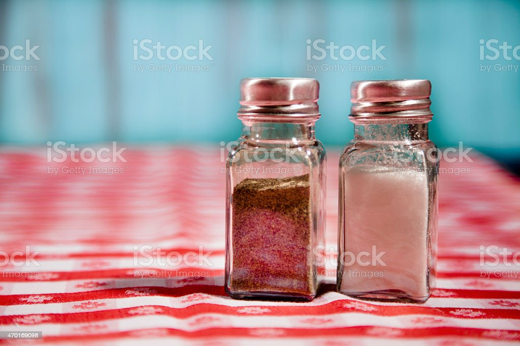 Salt and pepper shakers on red checked tablecloth. Picnic, restaurant. stock photo
