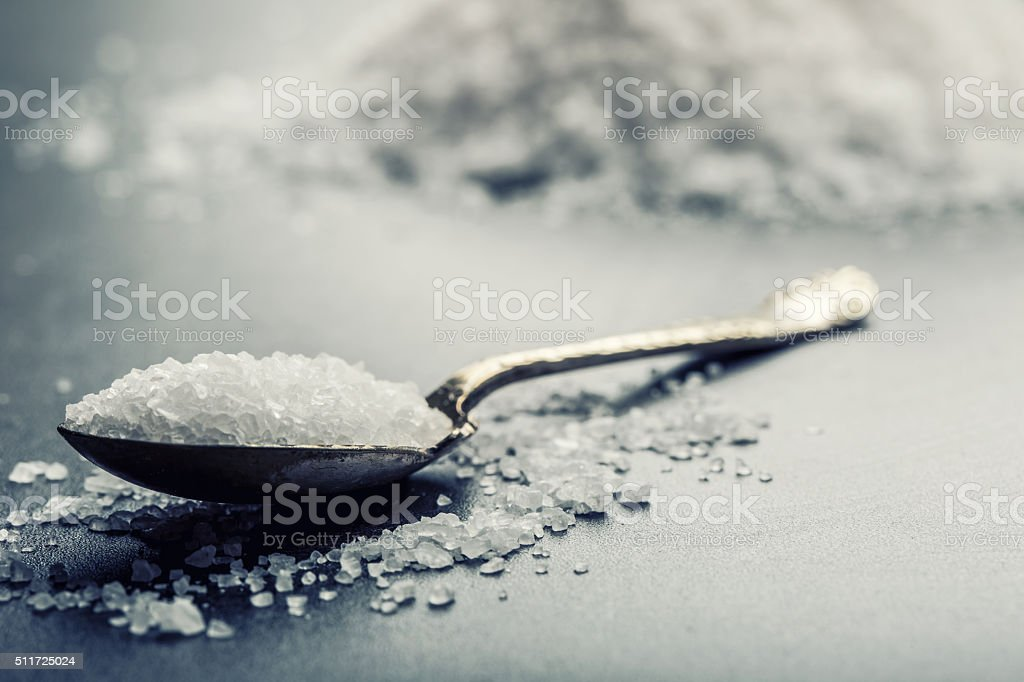 Salt. Coarse grained sea salt on granite background stock photo