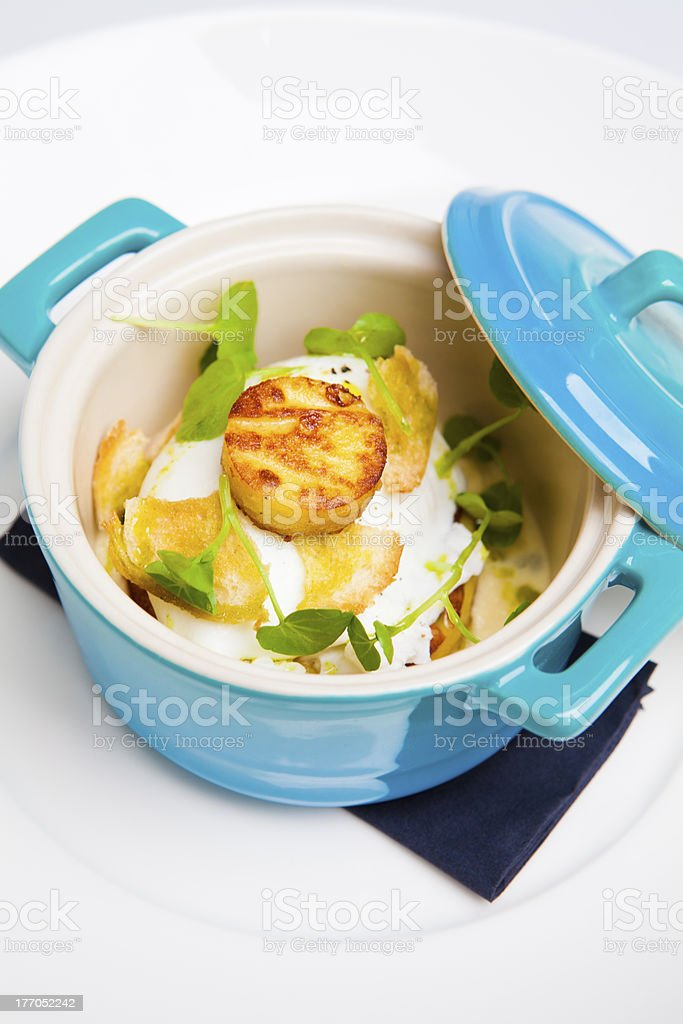 Salt cod with poached egg served in a turquoise pot royalty-free stock photo