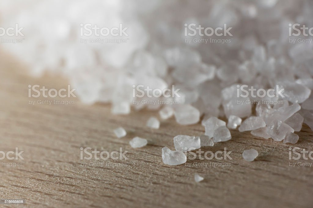 Salt crystals on wooden plate close up stock photo