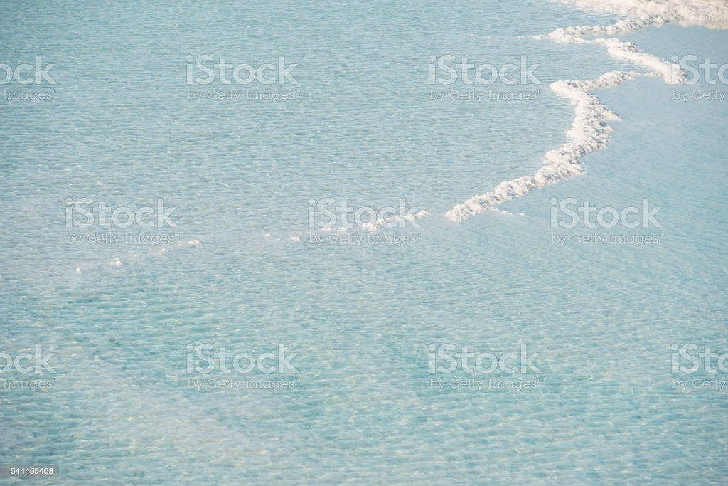 Salt crystals sticking out of the salty blue water. stock photo