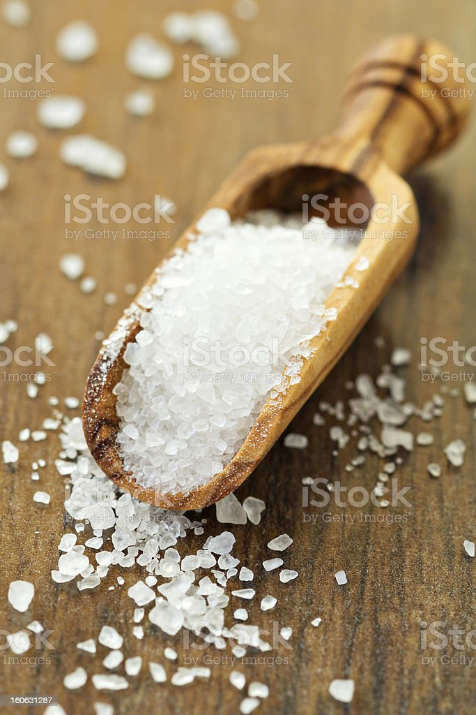 Salt in a wooden scoop stock photo