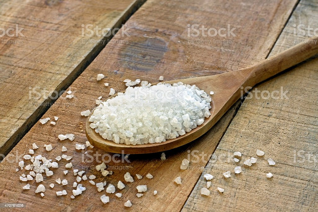 Salt in spoon on a wooden table stock photo