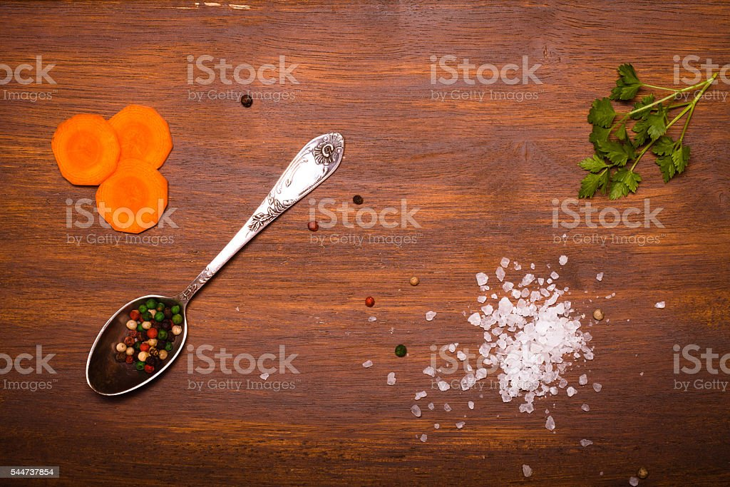 Salt, pepper and vegetables on old wood background. Toned stock photo