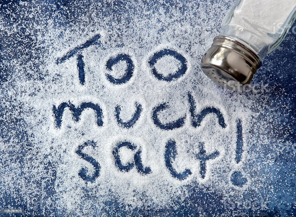 Salt spilled on a blue background with too much salt written stock photo
