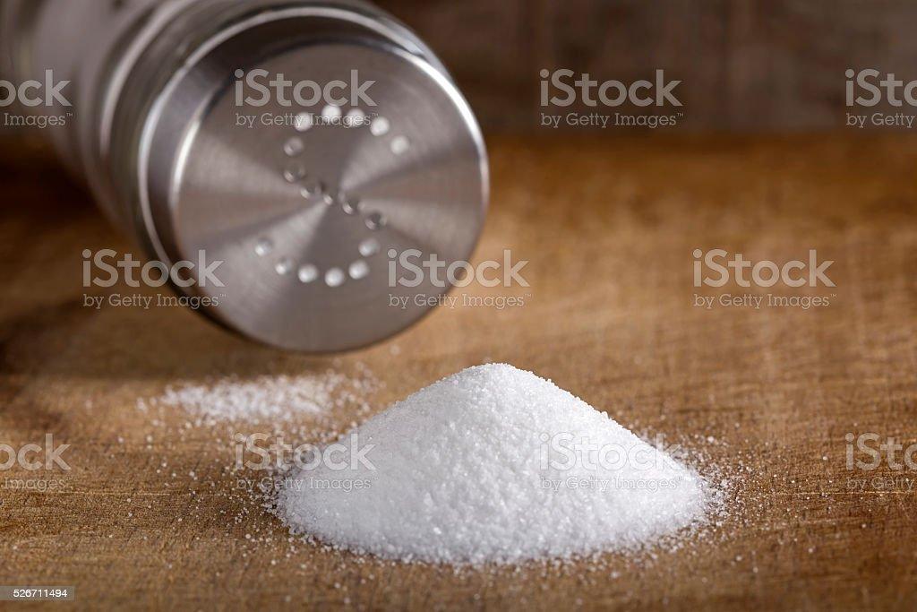 Salt spilling on table from salt cellar stock photo
