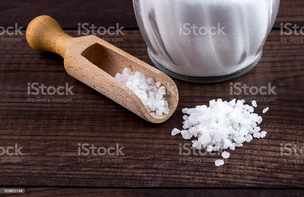 salt, wooden spoon and glass saltshaker on wooden table stock photo