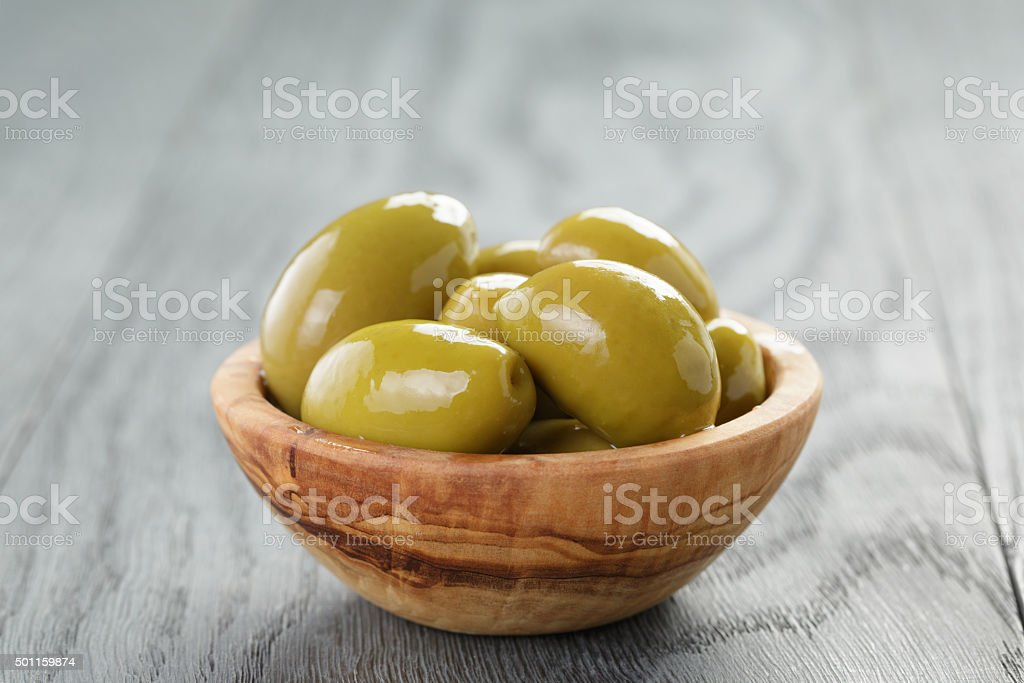 salted giant green olives in olive bowl on wooden table stock photo