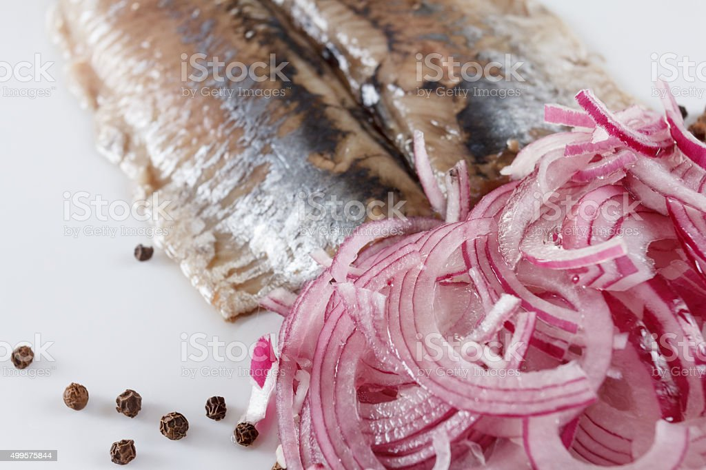 Salted herring on the plate with red onion stock photo