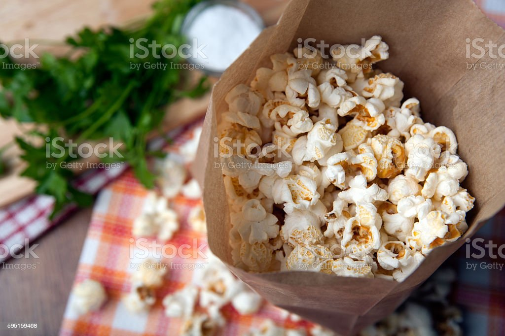 salted popcorn in a paper bag close up stock photo