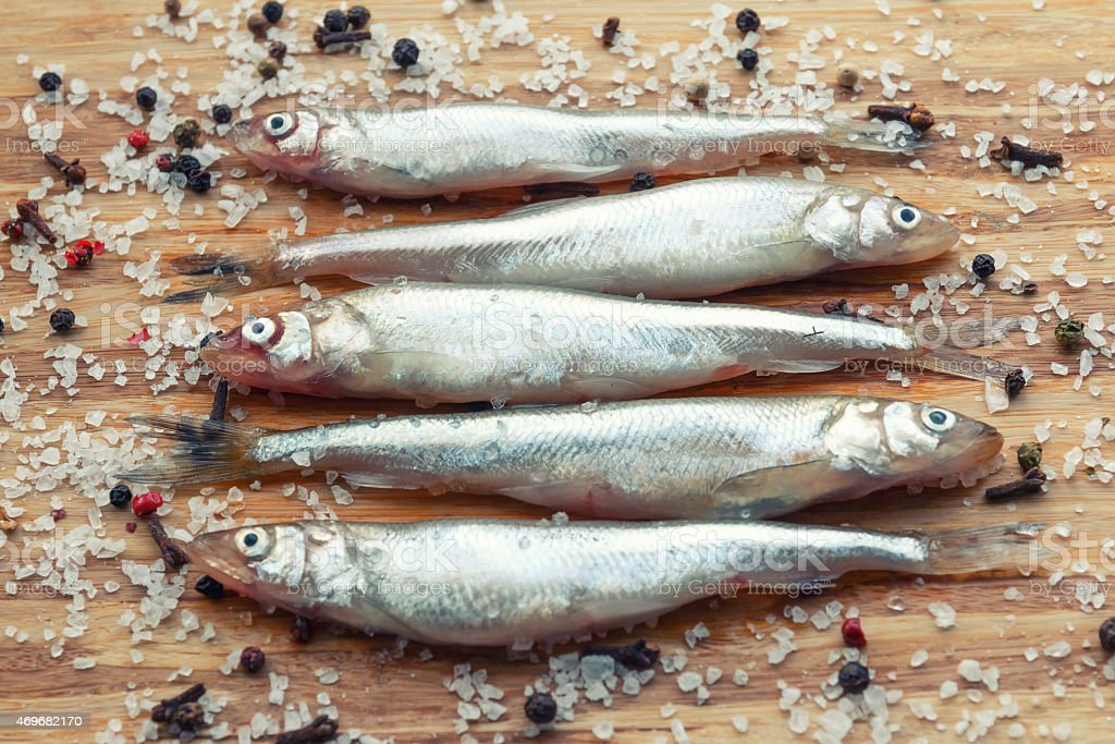 Salted sprats with salt and pepper on the board stock photo