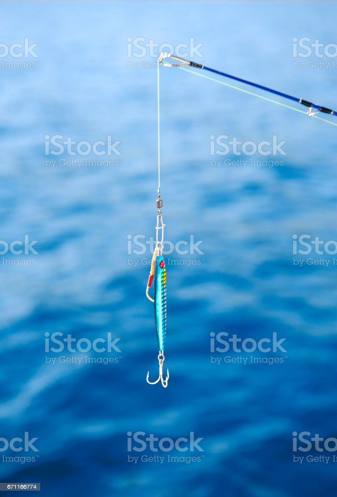 Saltwater fishing rod with wobbler and the sea background stock photo