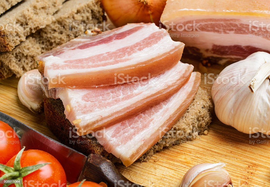 Salty piece of lard with cherry tomatoes. stock photo