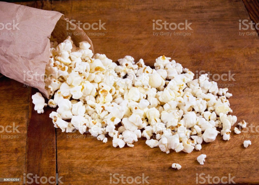 Salty popcorn in package on table stock photo