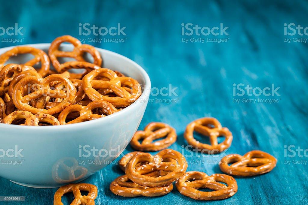 Salty snacks mini pretzels in bowl stock photo
