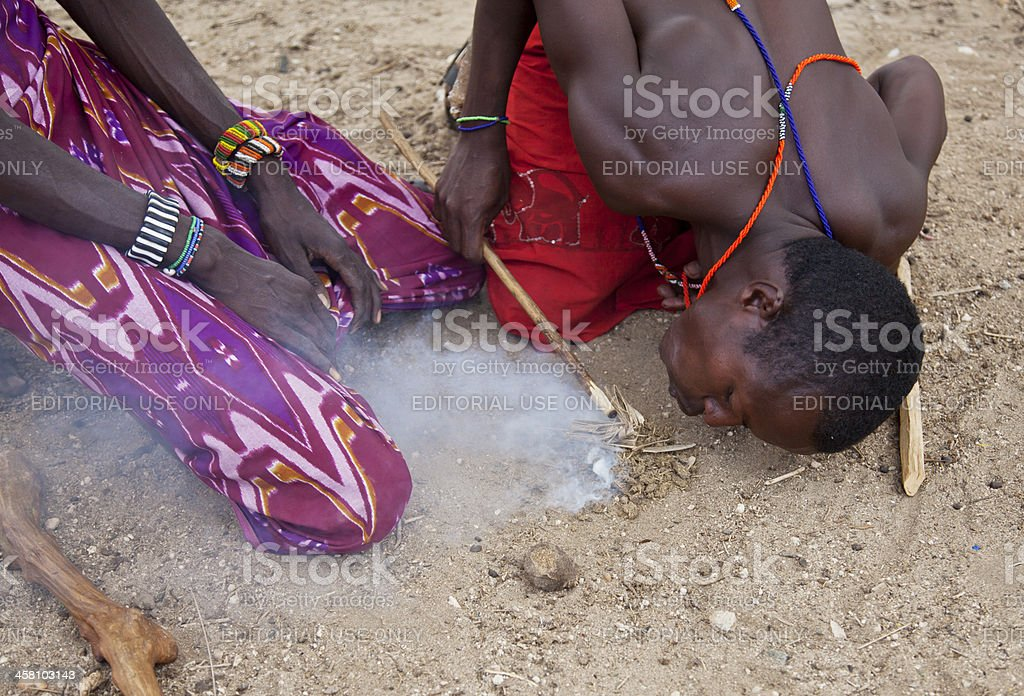Samburu men making fire with sticks and goats dung. royalty-free stock photo