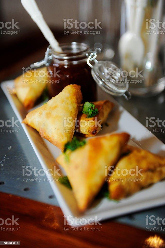 Samoosas on a plate with relish stock photo