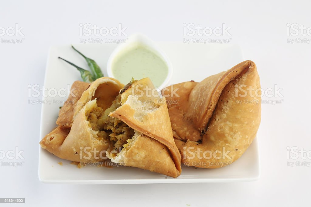 samosa with fresh mint dipping sauce , indian food stock photo