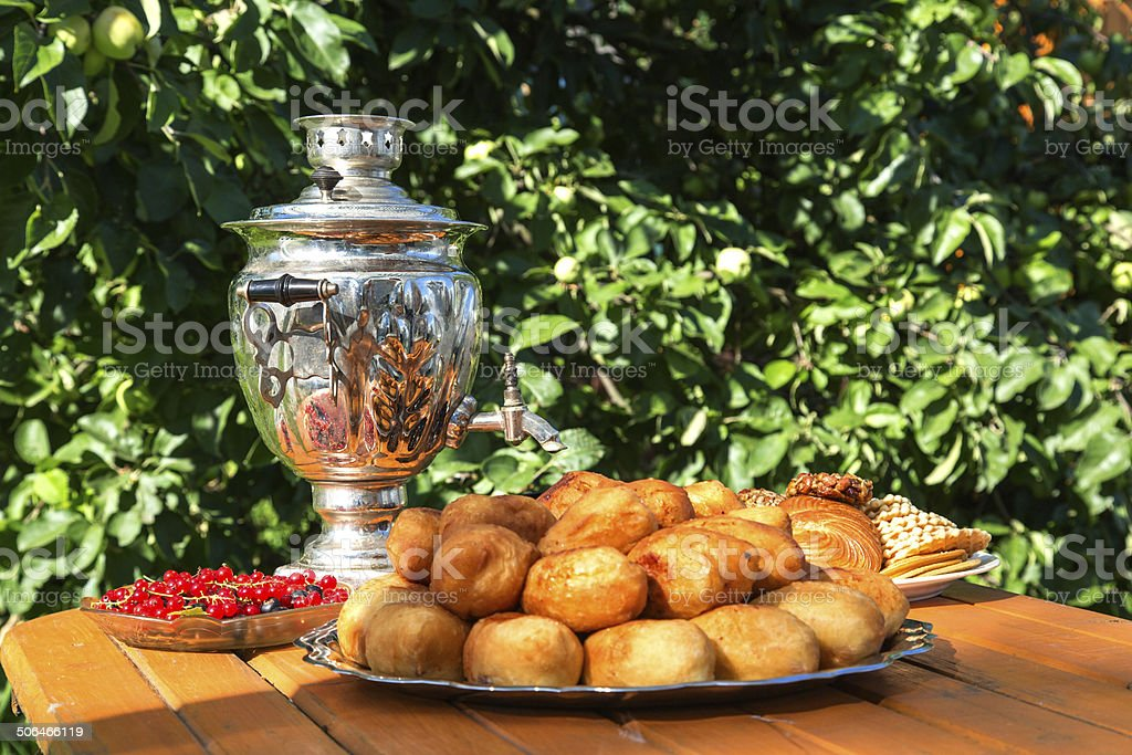 samovar on a wooden table with cakes and candies berries stock photo