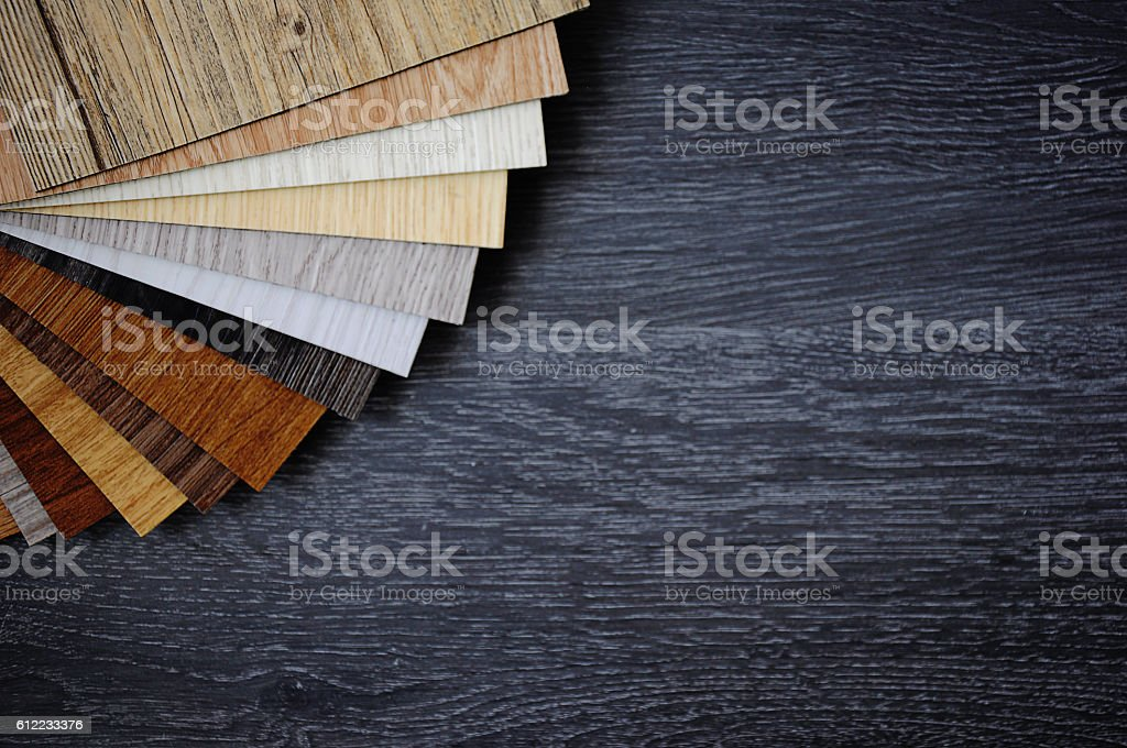 Sample pack of wooden flooring laminate on wooden black floor stock photo