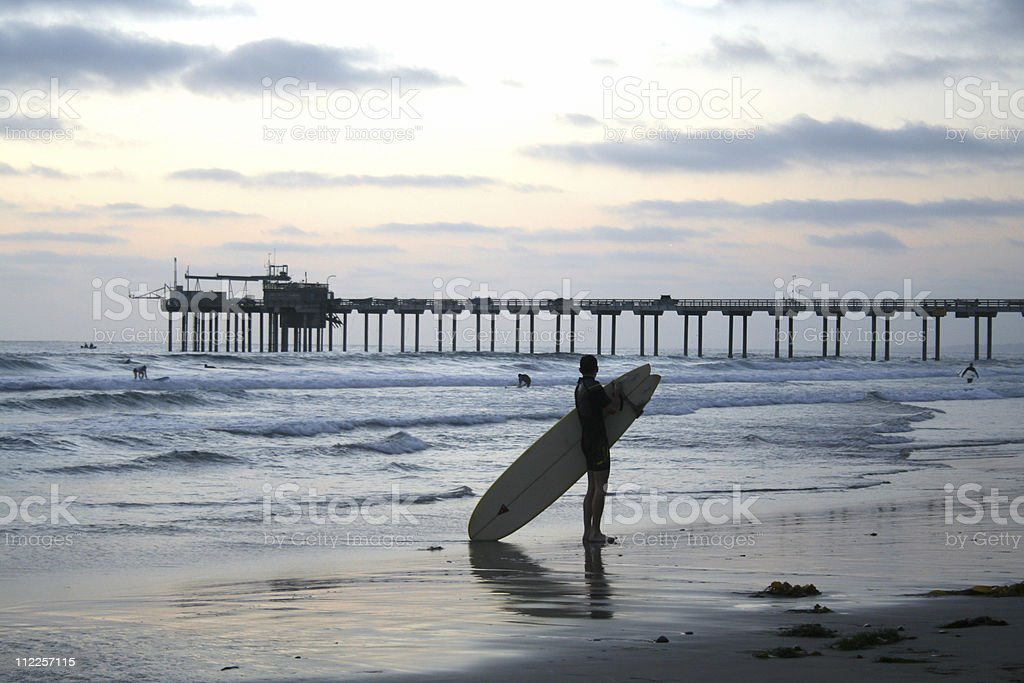 San Diego Surfer on Beach after Sunset with Pier royalty-free stock photo