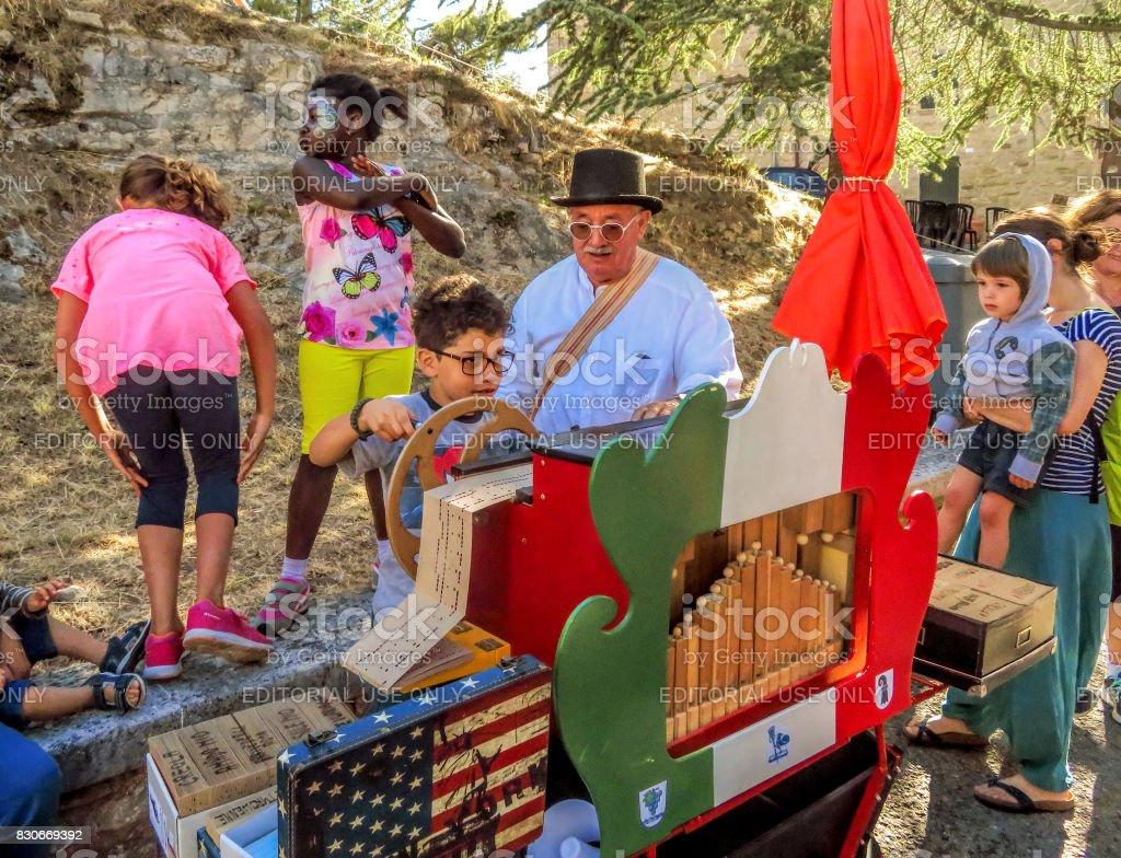 San Leo - Organ-grinder is teaching the children their craft stock photo
