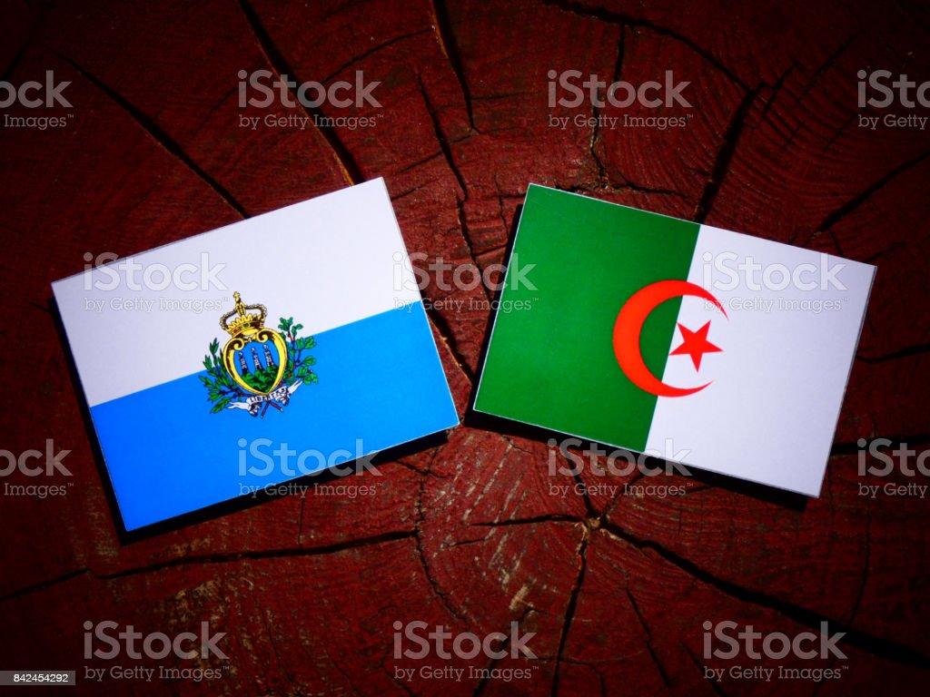 San Marino flag with Algerian flag on a tree stump isolated stock photo